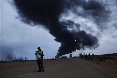 A supporter of Libya's leader Muammar Gaddafi holds his portrait near a blazing storage tank at a refinery in Ras Lanuf March 12, 2011. Editor's note: Picture taken on guided government tour. REUTERS/Chris Helgren