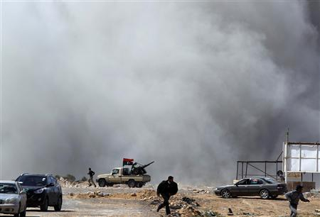 Rebels fighters run for cover during an air strike at a rebel fighters checkpoint in Al Ugaila area along a road between the towns of Brega and Ras Lanuf, March 12, 2011. REUTERS/Goran Tomasevic