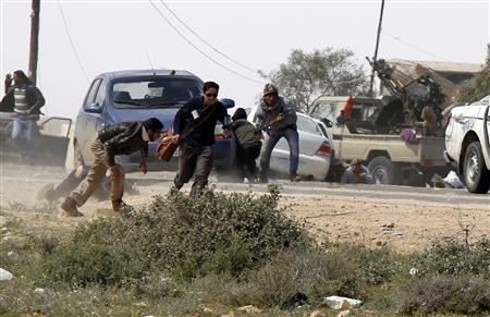 Rebels and foreign journalists take cover during an air strike at a rebel fighters checkpoint in Al Ugaila area along a road between the towns of Brega and Ras Lanuf March 12, 2011. REUTERS/Goran Tomasevic