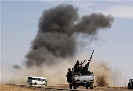 A rebel fighter gestures as he sits on a truck with an anti-aircraft gun during an air strike at a rebel fighters checkpoint in Al Ugaila area along a road between towns of Brega and Ras Lanuf, March 12, 2011. REUTERS/Goran Tomasevic