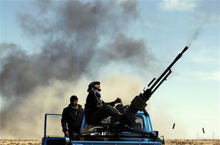A rebel fighter sits on a truck as he fires an anti-aircraft gun during an air strike at a rebel fighters checkpoint in Al Ugaila area along a road between the towns of Brega and Ras Lanuf, March 12, 2011. REUTERS/Goran Tomasevic