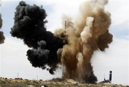 Smoke rises during an air strike at a rebel fighters checkpoint in Al Ugaila area along a road between the towns of Brega and Ras Lanuf, March 12, 2011. REUTERS/Goran Tomasevic