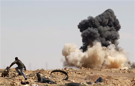 Foreign journalists and a rebel fighter take cover during an air strike at a rebel fighters checkpoint in Al Ugaila area along a road between the towns of Brega and Ras Lanuf, March 12, 2011. REUTERS/Goran Tomasevic