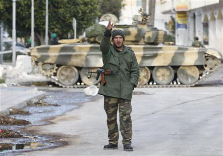 A Libyan soldier gestures in front of a tank at Martyr's Square in the centre of Zawiyah, west of the capital Tripoli, March 11, 2011. Editor's choice: Picture taken on guided tour. REUTERS/Ahmed Jadallah