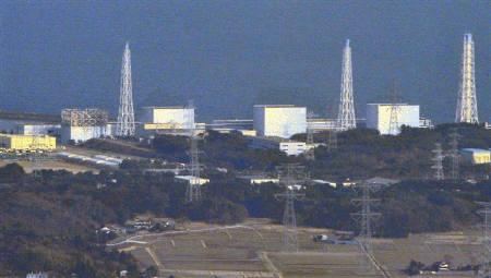 The damaged upper structure of Tokyo Electric Power Co.'s Fukushima Nuclear Plant reactor No. 1 (Left) and reactor No. 3 (Right) are pictured after an earthquake and tsunami struck the area, in Fukushima Prefecture in northern Japan March 13, 2011. REUTERS/Kyodo