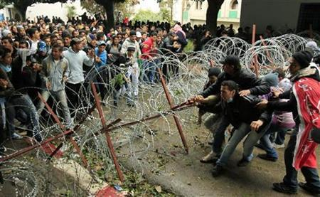 Tunisian protesters pull away barbed wire to let through the protesters on the other side of the police barricade near government offices in the Kasbah, the old city of Tunis, January 27, 2011. REUTERS/Zohra Bensemra