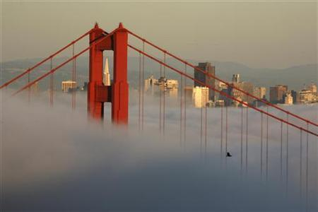 The skyline of San Francisco and the Golden Gate Bridge appear above the evening fog as the suns sets on the Marin Headlands in Sausalito, California April 18, 2009. REUTERS/Robert Galbraith