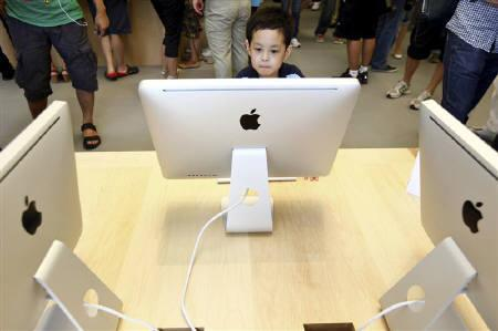 A boy looks at an Apple iMac desktop computer at the new Apple Store in Pudong Lujiazui, in Shanghai July 10, 2010.  REUTERS/Aly Song/Files