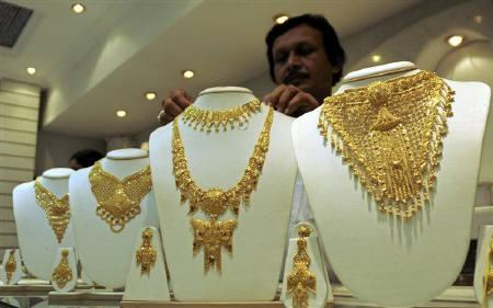 A salesman displays a gold necklace at a jewellery shop in Agartala, Tripura, July 9, 2009. REUTERS/Jayanta Dey/Files