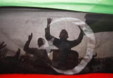 Protesters are seen through a Kingdom of Libya flag during celebrations after a U.N. resolution authorizing a ''no-fly'' zone, in Tobruk, east of Tripoli, March 18, 2011. REUTERS/Suhaib Salem