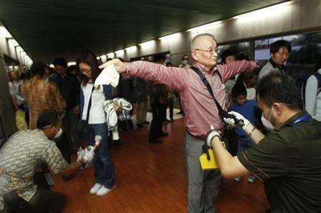 Members of the Indonesia Nuclear Energy Regulatory Agency (BAPETEN) scan passengers arriving from Japan for radiation exposure at the Sukarno-Hatta airport in Jakarta March 18, 2011. REUTERS/Supri