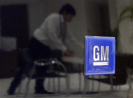 An employee is reflected in a General Motors' Chevrolet MW, made by Suzuki Motor, at a Suzuki Motor showroom in Tokyo June 2, 2009. REUTERS/Toru Hanai