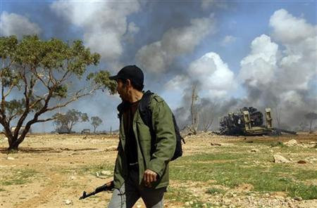 A rebel fighter looks at burning vehicles belonging to forces loyal to Libyan leader Muammar Gaddafi after an air strike by coalition forces along a road between Benghazi and Ajdabiyah March 20, 2011. REUTERS/Goran Tomasevic