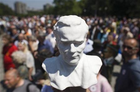 A supporter holds a statue of the late Yugoslav dictator Josip Broz Tito to mark his birth anniversary in Belgrade, May 25, 2010. REUTERS/Marko Djurica
