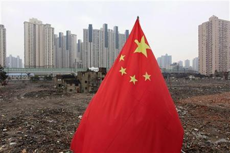 A Chinese national flag is seen in front of a residential site in downtown Shanghai March 4, 2010. REUTERS/Aly Song
