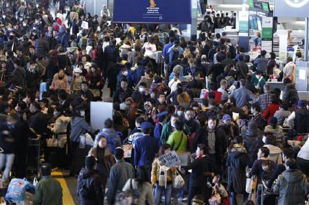 3月22日、東日本大震災による原発事故などを受け、国外に脱出する外国人が増える中、日本との強いつながりを感じて「第2の故郷」に留まる外国人もいる。成田空港で19日撮影(2011年 ロイター/Jo Yong-Hak)