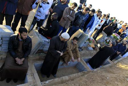 Libyans mourn during the funeral of the people who were killed after air strikes by coalition forces, at the martyrs' cemetery in Tripoli March 20, 2011. REUTERS/Ahmed Jadallah
