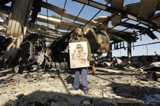 <p>A Libyan holds a poster of Libya's leader Muammar Gaddafi at a naval military facility damaged by coalition air strikes last night in eastern Tripoli, March 22, 2011. Editor's note: Picture taken on guided government tour. REUTERS/Zohra Bensemra</p>