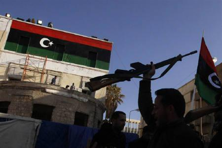 A man holds up a rifle in front of a Kingdom of Libya flag, during the funeral of a rebel killed by forces loyal to Libyan leader Muammar Gaddafi, in Ajdabiyah, in Benghazi March 22, 2011. REUTERS/Suhaib Salem