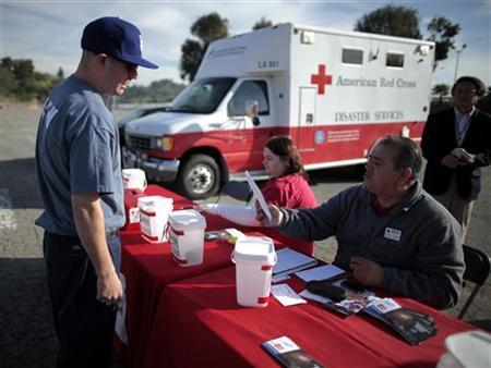 A man donates $325 at a drive-through relief event at Dodger Stadium to raise money for the American Red Cross Japan earthquake and tsunami relief efforts in Los Angeles, California March 15, 2011. REUTERS/Lucy Nicholson