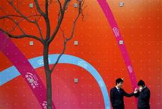 <p>A man lights a friend's cigarette as they stand in front of an advertisement for the China World shopping mall in central Beijing March 22, 2011. REUTERS/David Gray</p>