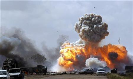 Vehicles belonging to forces loyal to Libyan leader Muammar Gaddafi explode after an air strike by coalition forces, along a road between Benghazi and Ajdabiyah, March 20, 2011. REUTERS/Goran Tomasevic
