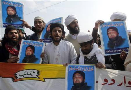 Supporters of various religious parties hold images of Malik Mumtaz Hussain Qadri while chanting slogans in support of Qadri, the gunman detained for the killing of Punjab Governor Salman Taseer, outside Adiala Jail in Rawalpindi February 26, 2011. REUTERS/Faisal Mahmood