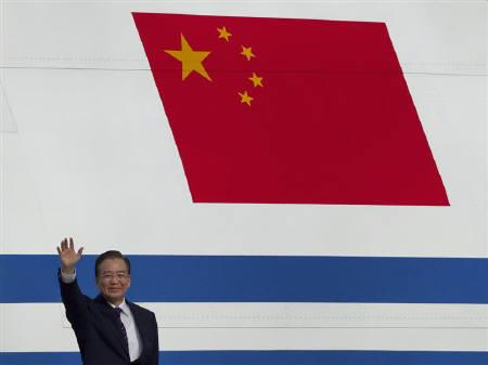 Chinese Premier Wen Jiabao waves in front of China's national flag, on the side of the aircraft that flew him to Pakistan, in Islamabad December 17, 2010.  REUTERS/Mian Khursheed/Files