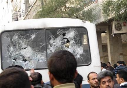 Syrians gather near a bus with shattered windows after shootings during a protest in Mouadamieh, near Damascus, March 25, 2011. REUTERS/Stringer