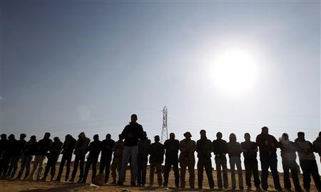 Rebel fighters pray along the Benghazi -Ajdabiyah road near Ajdabiyah March 24, 2011. REUTERS/Goran Tomasevic