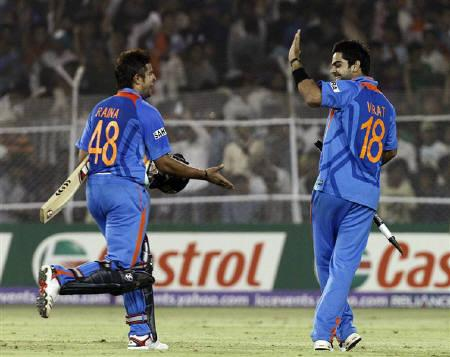 Suresh Raina (L) celebrates with teammate Virat Kohli after their Cricket World Cup 2011 quarter-final match against Australia in Ahmedabad March 24, 2011.                       REUTERS/Amit Dave