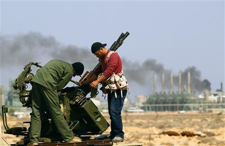 Rebel fighters fix their mounted anti-aircraft gun near the oil refinery at Ras Lanuf in Libya, March 27, 2011. REUTERS/Andrew Winning