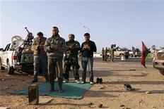 <p>Ливийские повстанцы молятся возле дороги к городу Рас-Лануф 27 марта 2011 года. Катар признал в понедельник руководящий орган ливийских повстанцев единственным законным представителем интересов ливийского народа, сообщило катарское государственное информагентство. REUTERS/Youssef Boudlal</p>