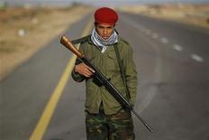 """<p>Ливийский повстанец стоит на дороге между городами Бин-Джавад и Навфалия, 29 марта 2011 года. Ливийские повстанцы в понедельник продвинулись дальше на запад страны в направлении родного города Муаммара Каддафи - Сирта, а президент США Барак Обама пообещал избирателям, что американские войска """"не застрянут"""" в Ливии, как в Ираке. REUTERS/Finbarr O'Reilly</p>"""
