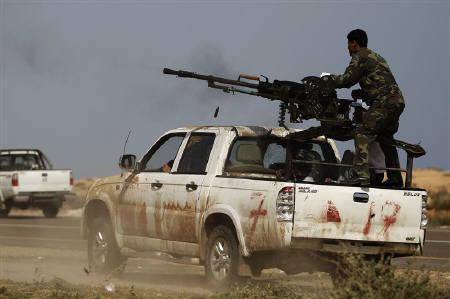 Rebel fighter returns fire after forces loyal to Muammar Gaddafi attacked them near Bin Jawad in eastern Libya, March 29, 2011. REUTERS/Finbarr O'Reilly