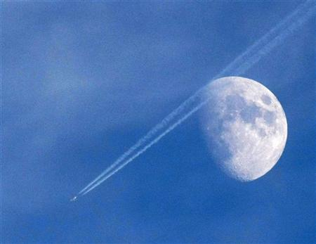 A passenger plane leaves a contrail as it flies past the moon over Malta September 18, 2010. REUTERS/Darrin Zammit Lupi