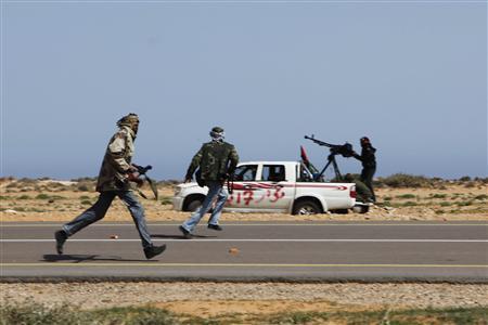 Rebel fighters run under machine gun fire and mortars after forces loyal to Muammar Gaddafi attacked them near Bin Jawad in eastern Libya, March 29, 2011. REUTERS/Finbarr O'Reilly