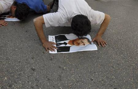 Syrian workers living in Lebanon kiss posters of President Bashar al-Assad laid out on the ground in front of the Syrian embassy in Beirut March 28, 2011. REUTERS/Mahmoud Tawil