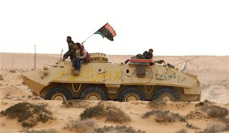 Rebel fighters drive east in a captured Armoured Personnel Carrier (APC) on the road between Ras Lanus and Brega, in Libya, March 29, 2011. REUTERS/Andrew Winning