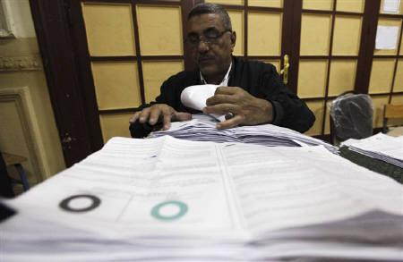 An official collects votes from ballot boxes after the polls closed in Cairo March 19, 2011. REUTERS/Mohamed Abd El-Ghany/Files