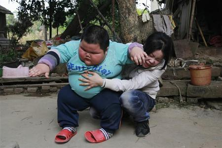 Lu Zhihao, 4, stands up from his mother's lap outside his house in Foshan, Guangdong province, China, March 29, 2011. Four-year-old Lu, who is 1.1m tall (3.6 feet) and weighs 62 kg (136 pounds), put on weight dramatically since his appetite grew when he was 3 months old. His worried parents took him to several hospitals, but the reason for his obesity remains unknown, though it is possibly due to his dietary habit, according to local media. REUTERS/Joe Tan