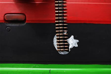 An ammunition belt hangs over a car door painted in the colours of the rebel Kingdom of Libya flag near Brega in eastern Libya March 30, 2011. REUTERS/Finbarr O'Reilly