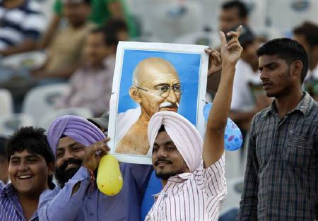 Members of the crowd hold up a portrait of Mahatma Gandhi and sing  in Mohali October 2, 2010. REUTERS/Andrew Caballero-Reynolds/Files