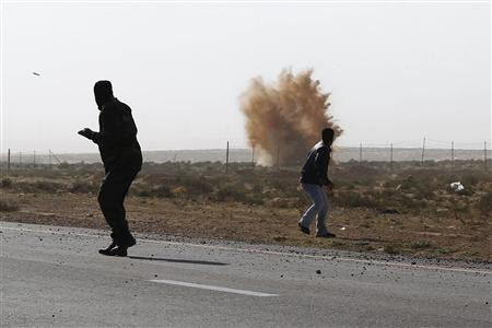 Rebels run from explosions during a mortar barrage fired by troops loyal to Muammar Gaddafi outside Brega in eastern Libya, April 1, 2011. REUTERS/Finbarr O'Reilly
