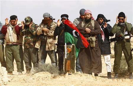 Rebel fighters pray at the grave of around 10 fellow rebels who were killed in what they say was a coalition airstrike on a group of vehicles on the road between Ajdabiyah and Brega, in Libya, April 2, 2011. REUTERS/Andrew Winning