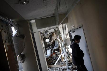 Tsunami survivor Takako Suzuki, 40, walks through the ruins of a civic hall in Rikuzentakata after she came with reporters to tell her story April 2, 2011. REUTERS/Damir Sagolj