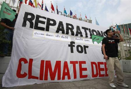 Activists from Jubilee South-Asia/Pacific Movement on Debt and Development (JSAPMDD) shout slogan near a banner during a demonstration in front of the United Nations building, the venue of climate talks, in Bangkok April 3, 2011. REUTERS/Chaiwat Subprasom