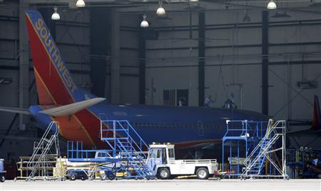 Southwest mechanics work on a Boeing 737 inside a hanger at the Phoenix Sky Harbor International Airport, April 2, 2011. REUTERS/Rick Scuteri
