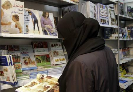 A visitor browses through books at a book fair near Damascus July 31, 2010. Syria lifted on Wednesday a ban on teachers wearing the full face veil and ordered the closure of a casino, moves aimed at placating conservative Muslims in the tightly-controlled country that has seen weeks of unrest. REUTERS/Khaled al-Hariri/Files