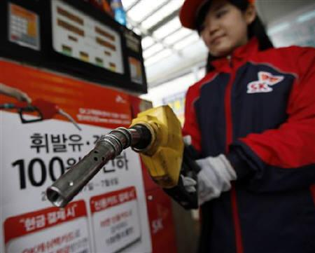 An employee holds a gas pump to refill a car at a petrol station during a photo opportunity in Seoul April 6, 2011. REUTERS/Lee Jae-Won/Files